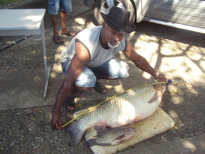 pescador mede peixe