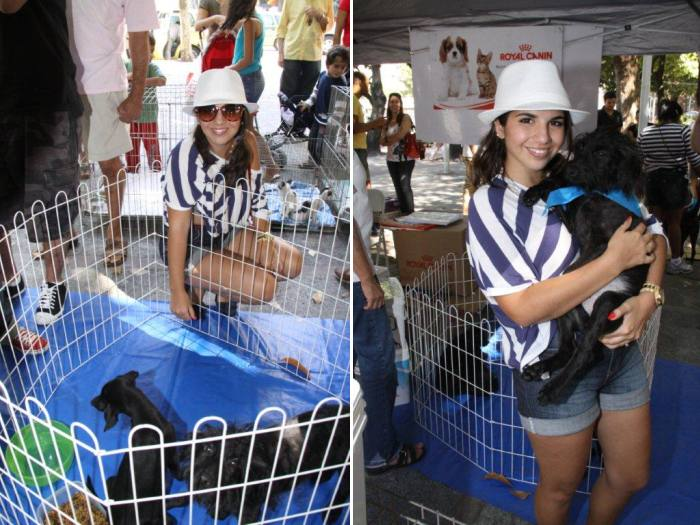 Natália Soutto, atriz, dá carinho a um cãozinho preto com um lenço azul amarrado no pescoço. Uma fofura!