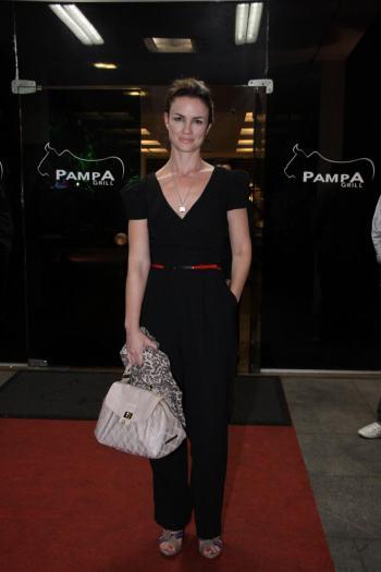 A atriz Carolina Kasting usou um macacão preto com decote v. Ela completou o look com sandálias de tiras mais grossas e um cinto fininho vermelho marcando ...