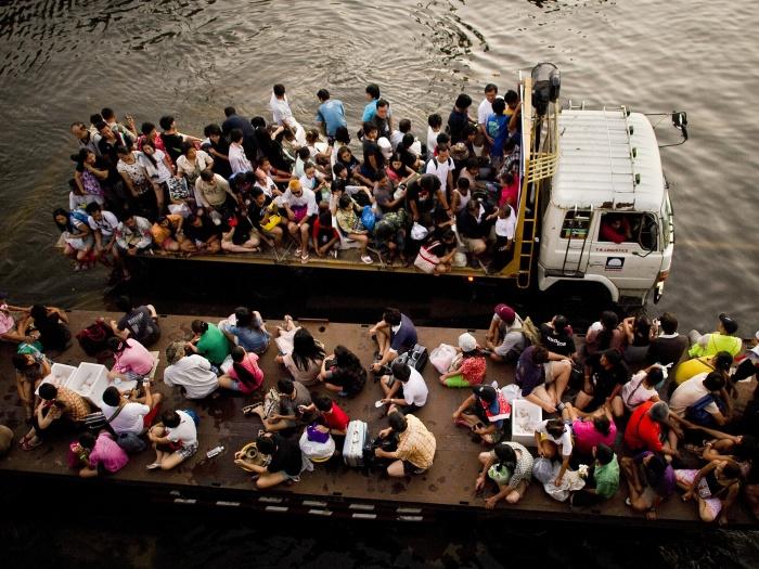 Na foto, pessoas cruzam regiões alagadas na traseira de um caminhão. Devido às inundações, está difícil a chegada de água potável e mantimentos às vítimas....