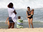Cláudia Abreu curte praia com a família